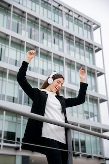 Mulher feliz usando fones de ouvido tiro médio