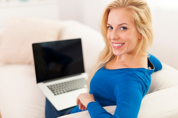 Mulher feliz usando laptop em casa