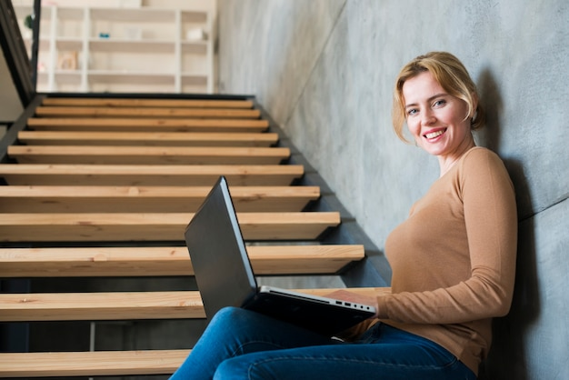 Mulher feliz usando laptop nas escadas