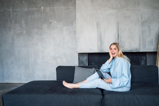Mulher feliz usando laptop prata enquanto está sentado no sofá
