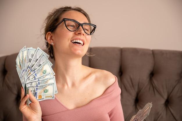 Mulher feliz usando óculos escuros, mostrando dinheiro