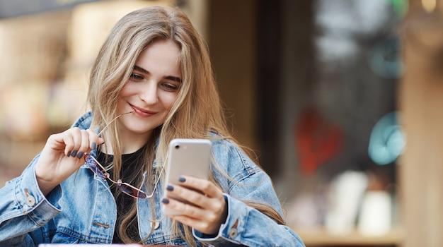 Mulher feliz usando smartphone em um café fast-food de rua, sorrindo w