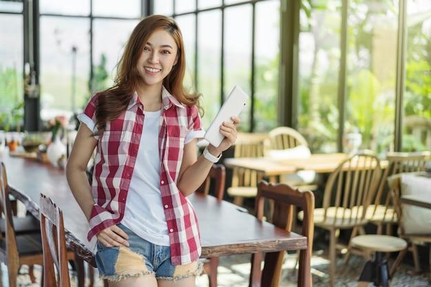 Mulher feliz usando tablet digital no café