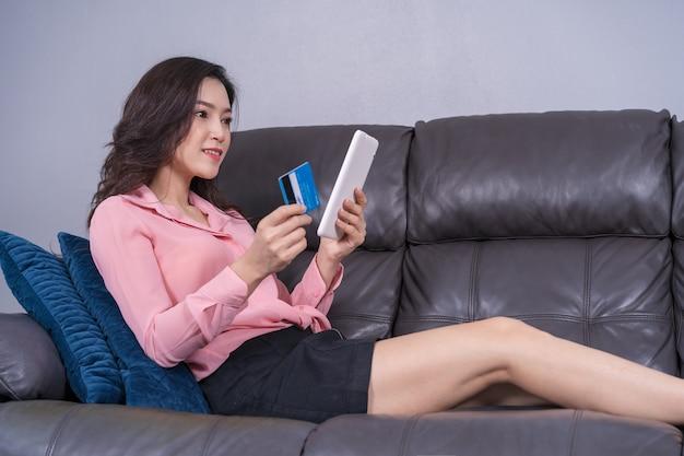 Mulher feliz usando tablet digital para compras on-line com cartão de crédito na sala de estar