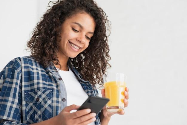 Mulher feliz usando telefone e segurando o suco de laranja