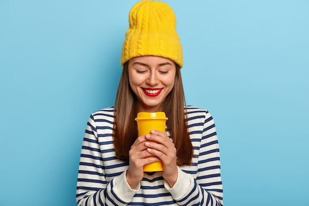 Mulher feliz usando um chapéu amarelo elegante e um macacão listrado, segurando um café para viagem, tem os lábios pintados de vermelho e gosta de uma bebida aromática