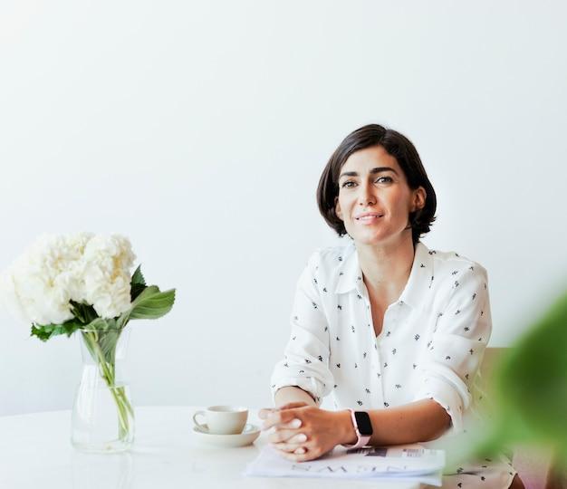 Mulher feliz usando um smartwatch sentada em sua mesa