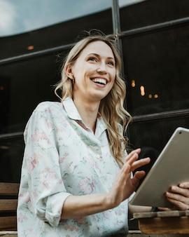 Mulher feliz usando um tablet digital ao ar livre