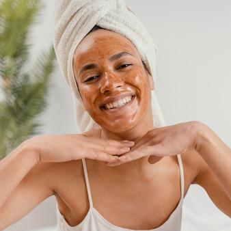 Mulher feliz usando uma máscara facial natural