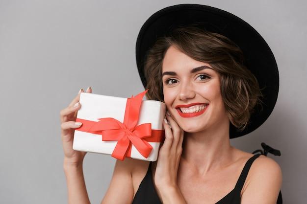 Mulher feliz usando vestido preto e chapéu segurando uma caixa de presente, isolada sobre uma parede cinza