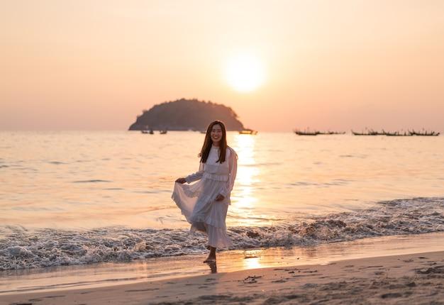 Mulher feliz vai viajar numa praia tropical de areia no verão