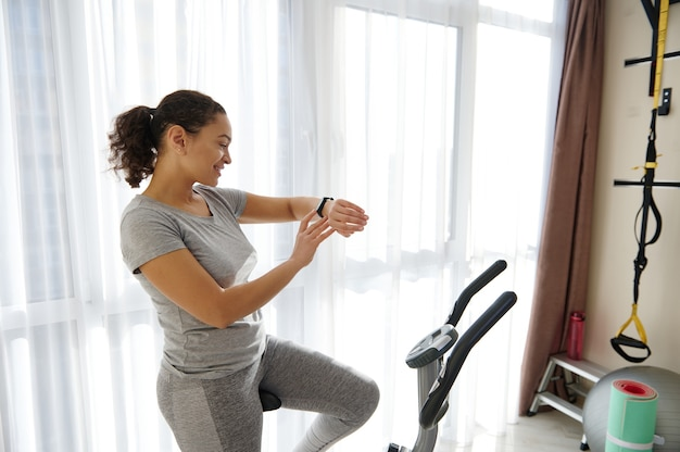 Mulher feliz, verificando o monitor de condicionamento físico e a frequência cardíaca em pé em uma bicicleta de spin após treino cardiovascular