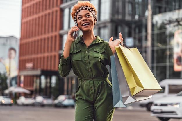Mulher feliz vestida com elegância nas ruas da cidade enquanto fala ao celular