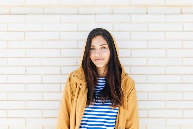 Mulher feliz vestindo jaqueta de pé contra a parede de tijolos