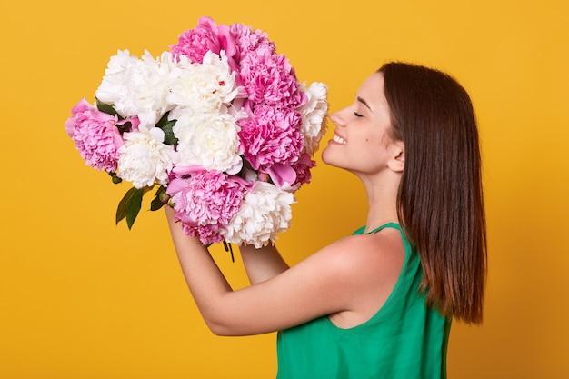 Mulher feliz vestindo traje verde segurando e cheirando flores peônias brancas e rosa