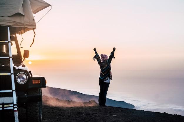 Mulher feliz viaja com carro e tenda em lugares selvagens apreciando o pôr do sol no topo de uma montanha