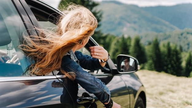 Mulher feliz viaja de carro nas montanhas. conceito de férias de verão