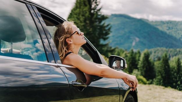 Mulher feliz viaja de carro nas montanhas