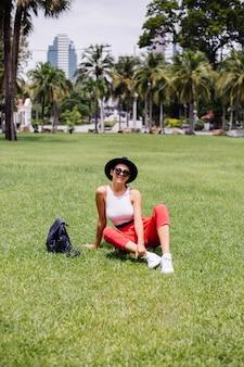 Mulher feliz viajando por bangkok com uma mochila, aproveitando um lindo dia de sol no parque tropical em um campo de grama verde