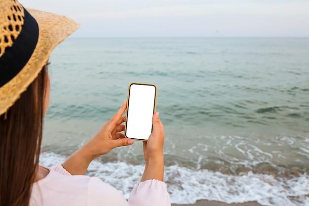 Mulher feliz viajante de vestido rosa usando telefone celular na praia tropical. conceito de verão, férias, tecnologia e estilo de vida. simulação de tela branca.