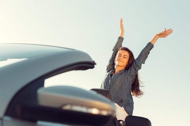 Mulher feliz viajante no carro cabrio