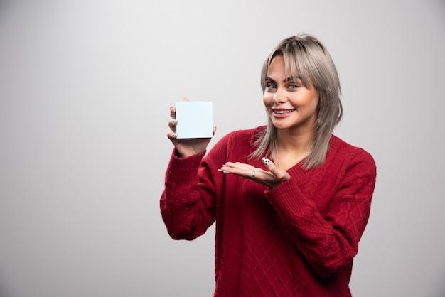Mulher felizmente mostrando bloco de notas em fundo cinza.