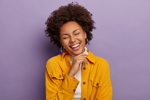 Mulher feminina encantadora ri de felicidade, toca o queixo e sorri positivamente, sente-se aliviada e alegre, veste uma jaqueta amarela da moda, isolada sobre fundo roxo.