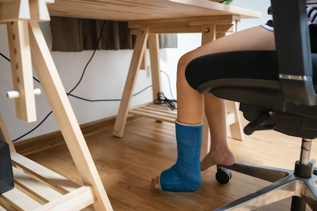 Mulher ferida com perna quebrada em molde de gesso trabalhando em uma mesa de madeira