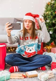 Mulher festiva fazendo beicinho enquanto toma selfie