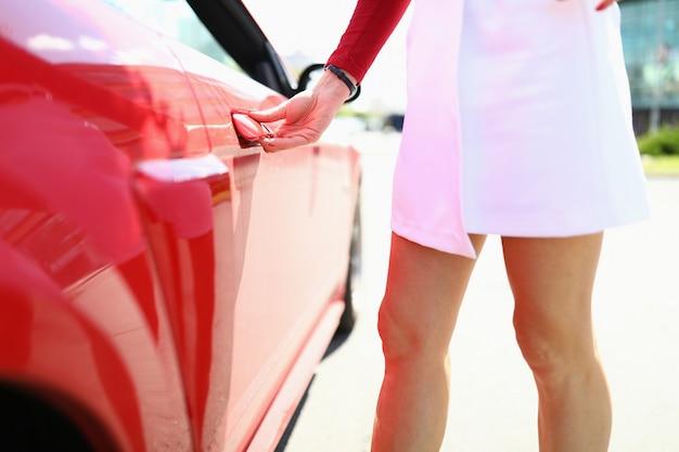 Mulher fica ao lado da mão do carro vermelho na maçaneta da porta.