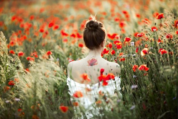 Mulher fica com as costas nuas, há uma flor de papoula tatuagem, entre o campo de papoulas