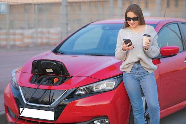 Mulher fica com telefone perto de seu carro elétrico e aguarda quando o veículo será cobrado. carregamento de carro elétrico