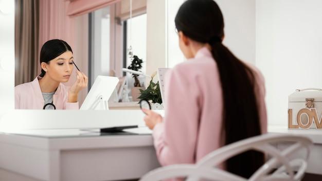Mulher fica em casa usando maquiagem