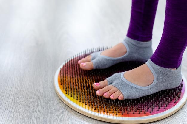 Mulher fica em pé em uma prancha com unhas pernas de mulher iogue fecham a prática de ioga