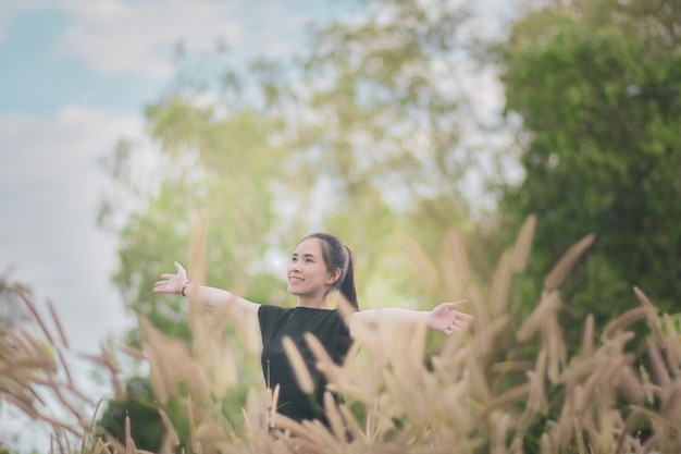 Mulher fica em uma floresta linda prado em uma atmosfera relaxante com a natureza.