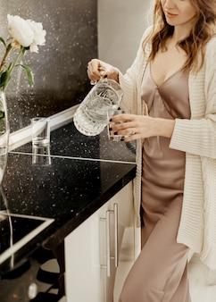 Mulher fica na cozinha e derrama água em um copo de uma jarra de vidro