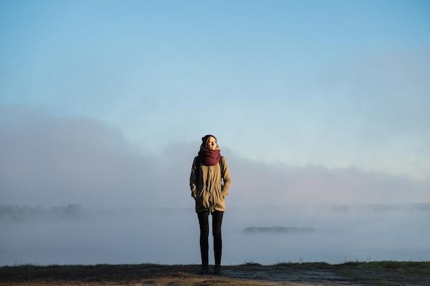 Mulher fica na luz do sol da manhã na frente de um cenário de bela natureza coberto de névoa. alpinista curtindo o sol nascente em um fundo natural enevoado