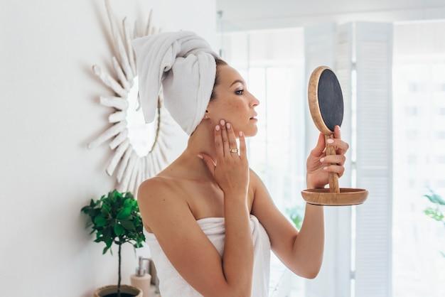 Mulher fica no banheiro e se olha em um pequeno espelho.