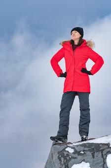 Mulher fica no topo de uma montanha rochosa, contra o céu com nuvens dramáticas como pano de fundo. conceito, copie o espaço para a indústria do turismo. jovem vestida com uma jaqueta vermelha de inverno, calças esportivas e botas de trekking