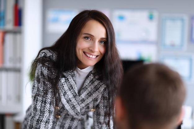 Mulher fica perto de um homem no escritório e sorri