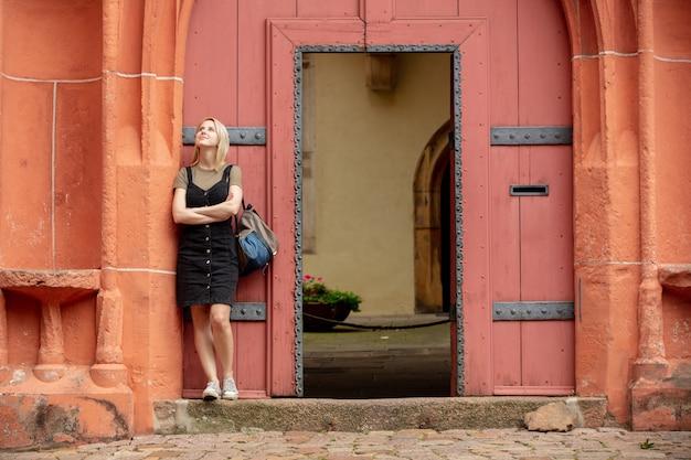 Mulher fica perto de velhas portas vermelhas em estilo romano na europa
