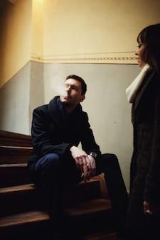 Mulher fica perto do homem que se senta na escada
