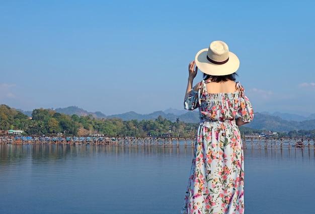 Mulher ficando impressionada com mon bridge, distrito de sangkhlaburi, tailândia