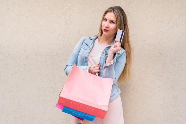 Mulher, ficar, com, bolsas para compras, e, cartão crédito, em, parede