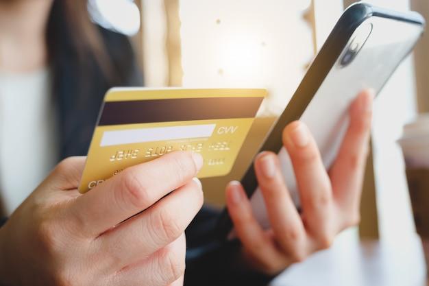 Mulher ficar em casa e mão usando cartão de crédito e telefone para compras on-line. conceito de marketing de negócios online.