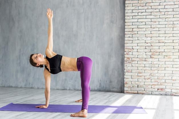Mulher, ficar, em, um, estendido, lado, ângulo, ioga posa