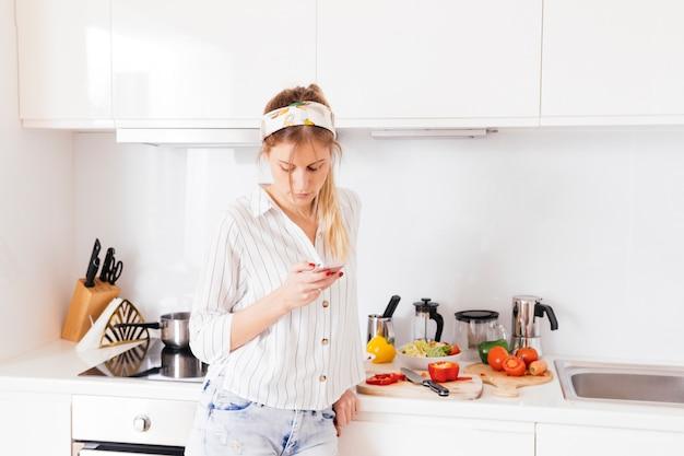 Mulher, ficar, perto, a, cozinha, worktop, usando, telefone móvel
