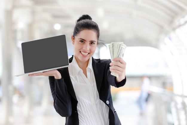 Mulher, ficar, segurando, trabalhando, com, um, laptop, e, dinheiro