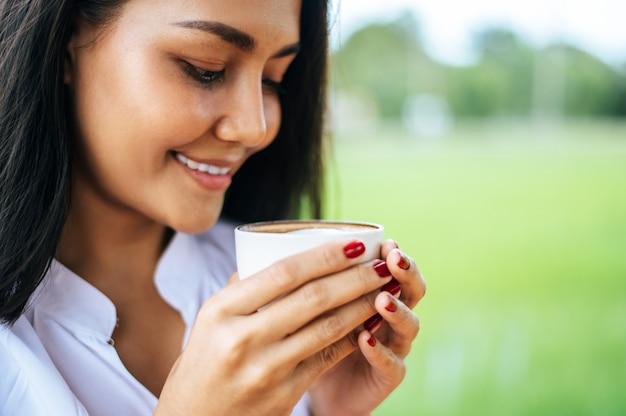 Mulher ficou alegremente tomando café no prado