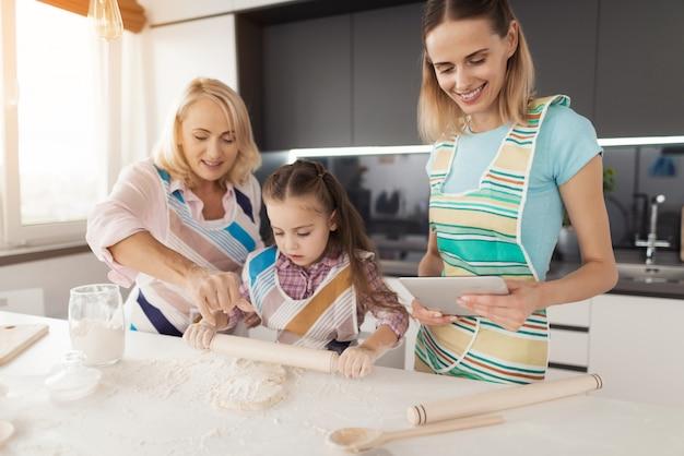 Mulher, filha e avó preparam produtos de panificação.